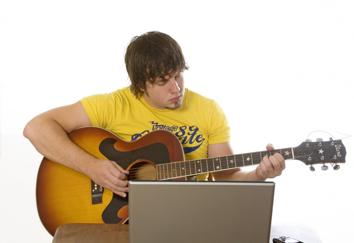 young man sitting on a laptop and plays guitar
